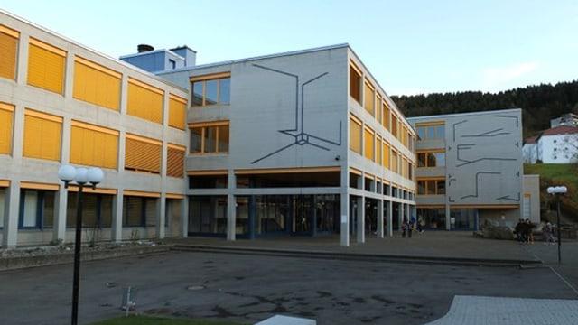 Schulhaus mit mehreren aneinandergebauten Gebäuden mit gelben Rolladen.