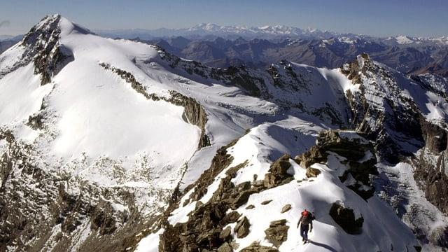 Ein Bergsteiger geht einem Grat entlang.