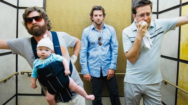 3 Männer stehen im Lift - ein Mann trägt ein Baby im Tragetuch