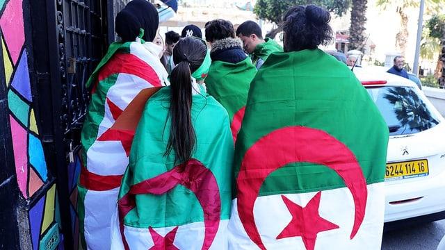 Junge Leute laufen auf der Strasse, sie tragen die Algerische Flagge auf dem Rücken.