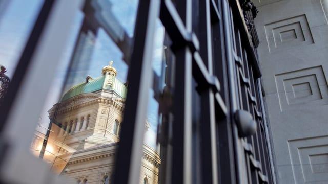 Bundeshaus spiegelt sich in Fenster von Nationalbank.