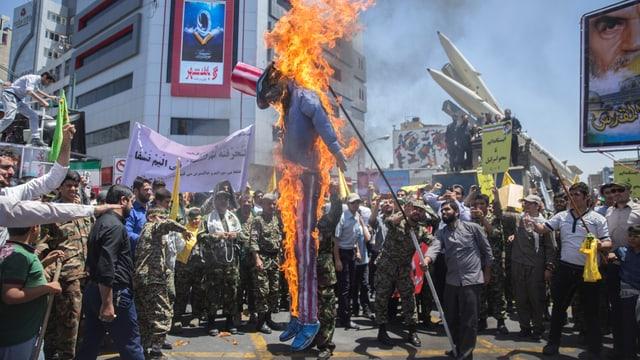 Demonstranten verbrennen eine Puppe mit USA-Hut