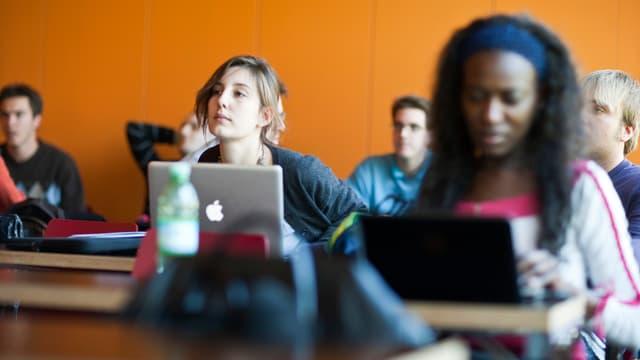 Studentinnen lauschen gebannt während einer Vorlesung.
