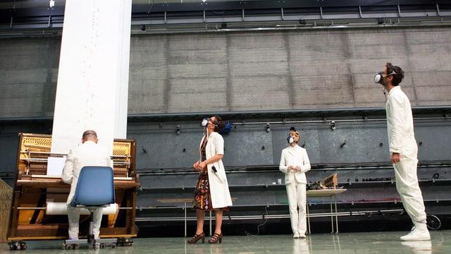 Blick auf eine Bühne, an einem Klavier ein Mann, den Rücken zugewandt, daneben stehen 3 Menschen in weissen Kitteln und mit Gasmaske.