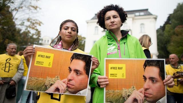 Zwei Frauen halten Fotos, die den inhaftierten Blogger Raif Badawi zeigen