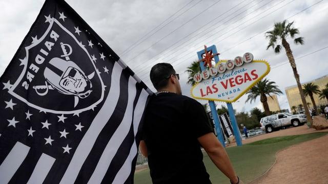 Ein Fan mit der Raiders-Fahne vor einem Las-Vegas-Schild.