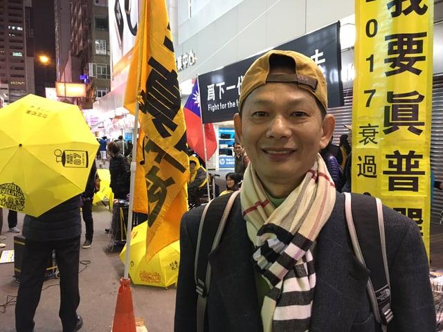 Ein junger Mann aus Hongkong steht vor gelben Fahnen und jemandem mit einem gelben Regenschirm.