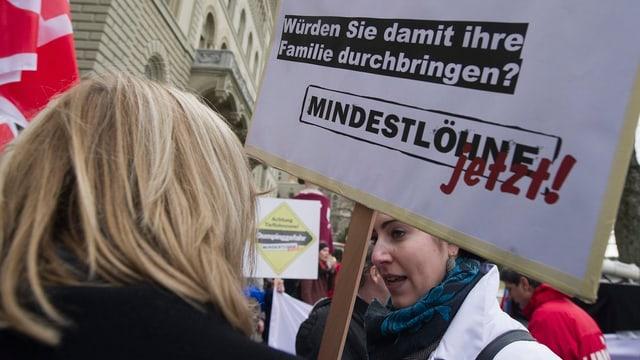 Eine Frau mit einem Transparent, das Mindestlöhne fordert.