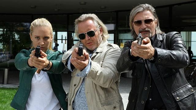 Eine Frau und zwei Männer halten ihre Waffe in die Kamera.