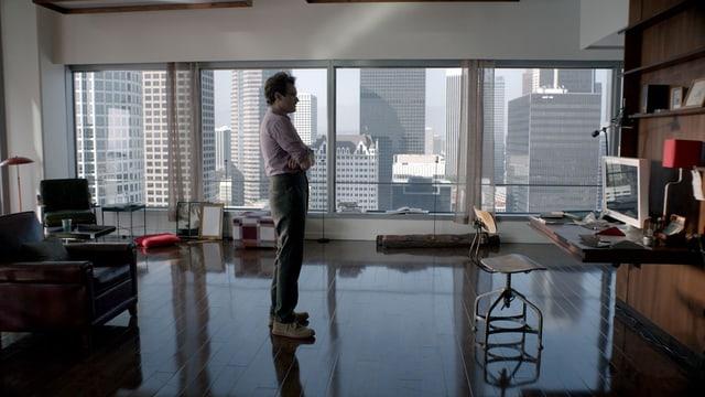 Mann wartend vor einem Computer in New Yorker Wohnung vor Fenster mit Skyline