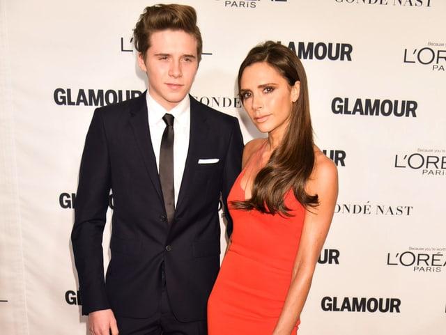 Brooklyn Beckham und Mama Victoria posieren vor einer Fotowand. Er im schwarzen Anzug, sie im roten Kleid.