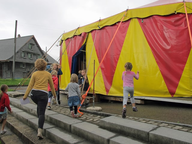 Kinder laufen auf Zirkuszelt zu