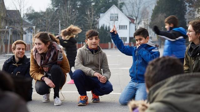 Kinder und Erwachsene kauern während eines Spiels auf dem Boden.
