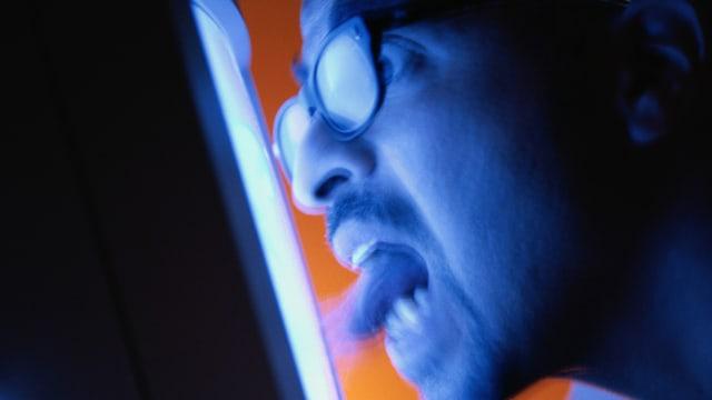Ein Mann mit Brille schaut mit geöffnetem Mund und grossen Augen in einen Monitor.