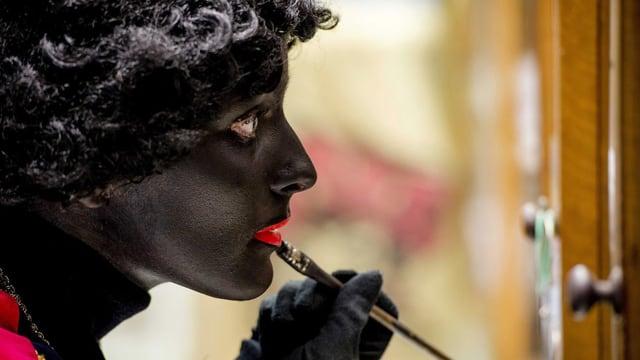 Eine Frau malt ihr Gesicht mit einem Pinsel schwarz an. Sie trägt eine dunkle Perücke.