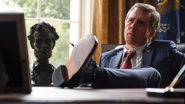 Sam Rockwell als George W. Bush mit den Füssen auf dem Pult des Oval Office.