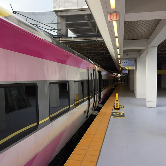 Ein neuer «Brightline Zug» mit rosa Streifen steht an einem Bahnhof in den USA. An den Ausgängen des Zuges wurden extra Warn-Pillonen aufgestellt, damit man nicht versehentlich stolpert.