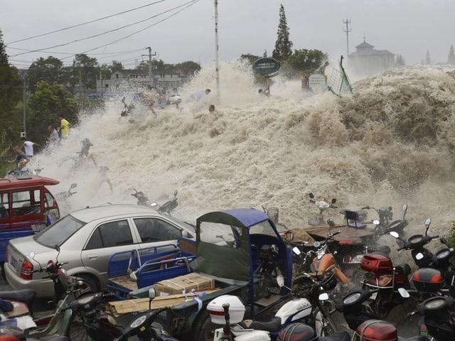 Menschen werden von der Gezeitenwelle über die Dammkrone gespült.