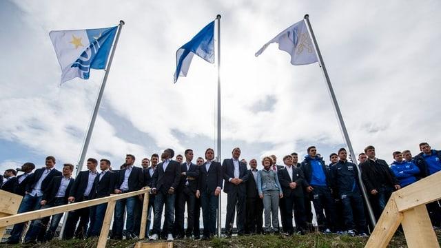 Eine Reihe Leute steht vor drei Flaggen von FCZ, GC und der Stadt Zürich.