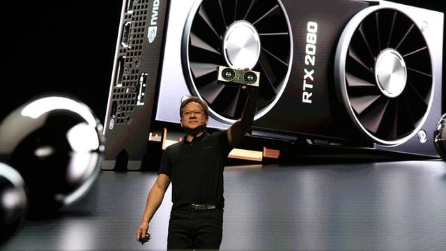 Der Nvidia-Chef, schwarze Hose, schwarzes T-Shirt, auf einer Bühne, hintendran die Projektion der neuen Grafik-Karte RTX 2080 - mit zwei riesigen Lüftern.