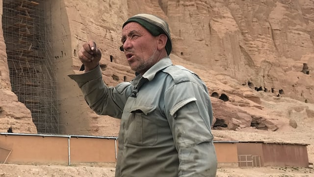 Mann vor Felswand mit Loch.