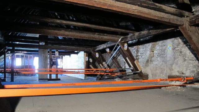 Dachstuhl eines alten Hauses mit quergespannten orangen Spanngurten