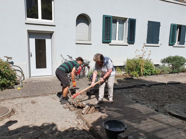 Eine Frau und ein Mann arbeiten im Garten.