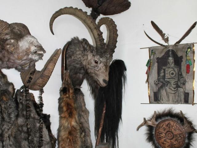 An der Wand hängen verschiedene Bilder und Tierelemente, darunter ein ausgestopfter Steinbock-Kopf.