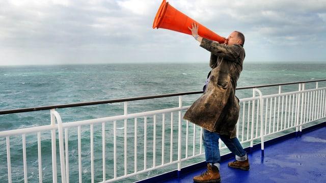 Ein steht an der Reling eines Schiffs und hält sich einen Leitkegel vor den Mund.