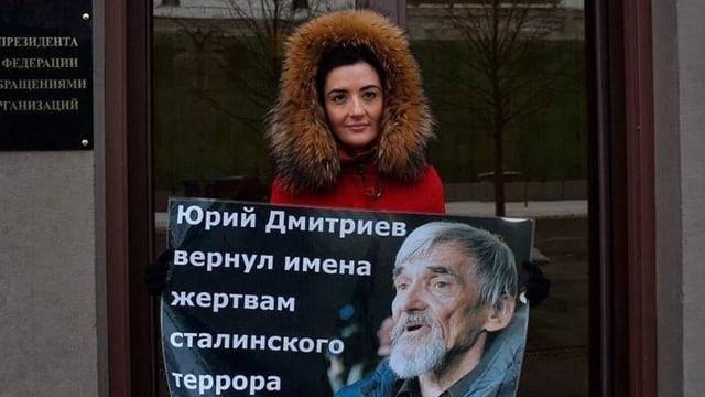 Eine Frau in Wintermantel hält ein Plakat.