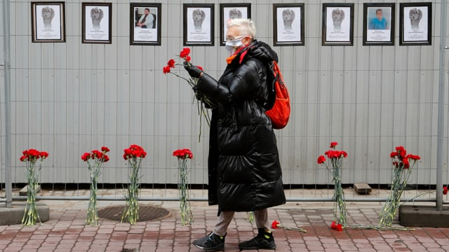 Frau mit Blumen vor einer Wand mit Fotos von Verstorbenen.
