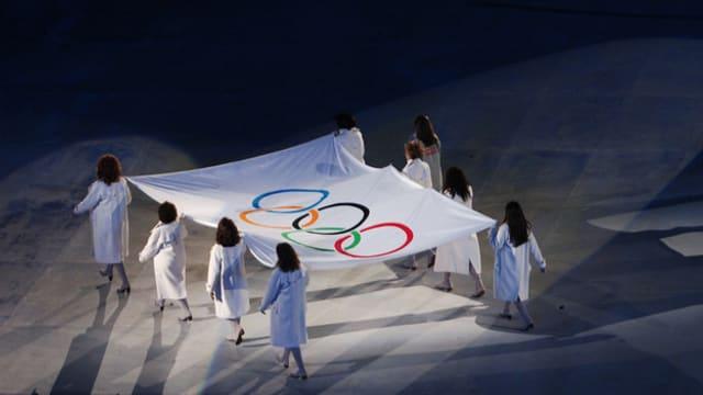 Die Olympische Flagge wird ins Stadion getragen.