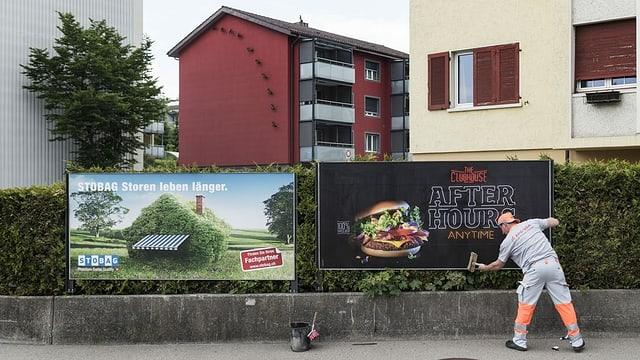Ein Mann klebt neue Plakate auf zwei Plakatwände in einer städtischen Umgebung.