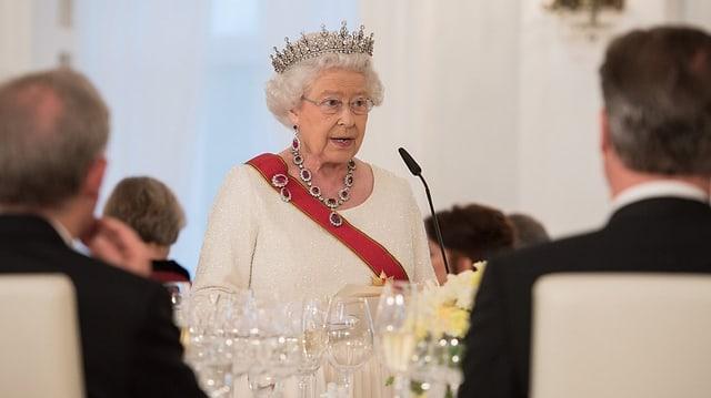Queen Elizabeth II. in weissem Kleid und mit Krone spricht vor Gästen an einem Tisch.