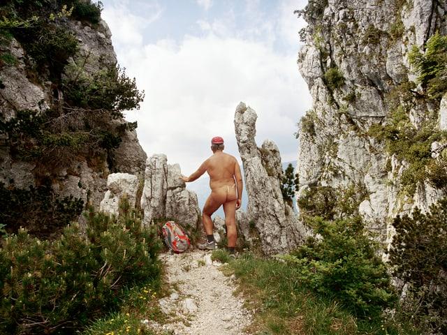 Ein Nacktwanderer blickt durch eine Felsschlucht in die Ferne.