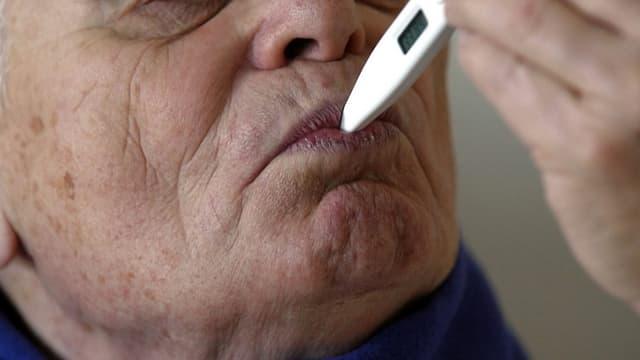 Ein Mann mit einem Fiebermesser im Mund.