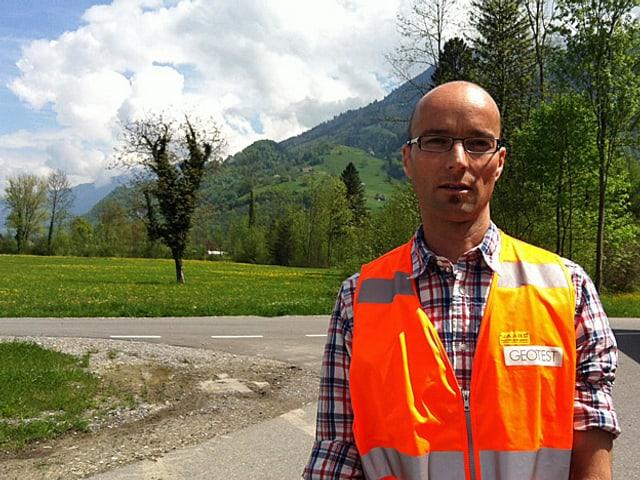 Stefan Tobler steht auf einer Wiese, im Hintergrund ist ein Berg.
