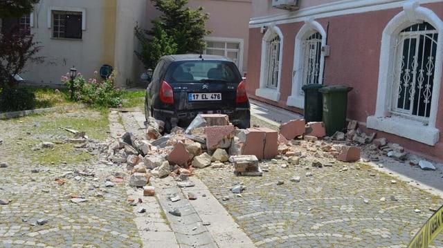 Steinstücke liegen in einem Innenhof vor einem Auto.
