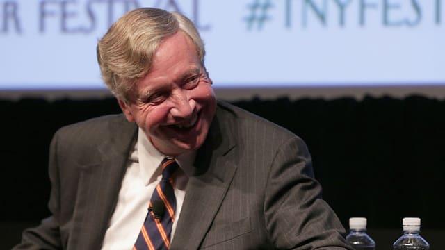 Ein Mann sitzt vor einer Leinwand und grinst.