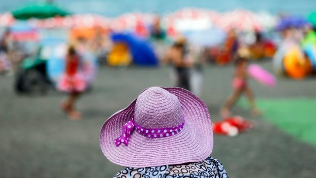 Frau mit violettem Hut steht am Strand