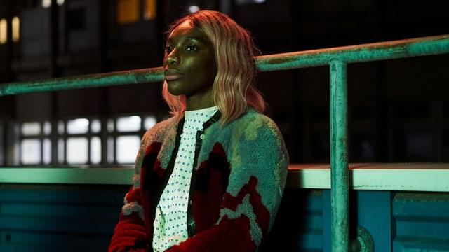 Frau sitzt mit nachdenklichem Blick auf einer Bank Sie trägt ein Nachthemd, darüber eine Strickjacke