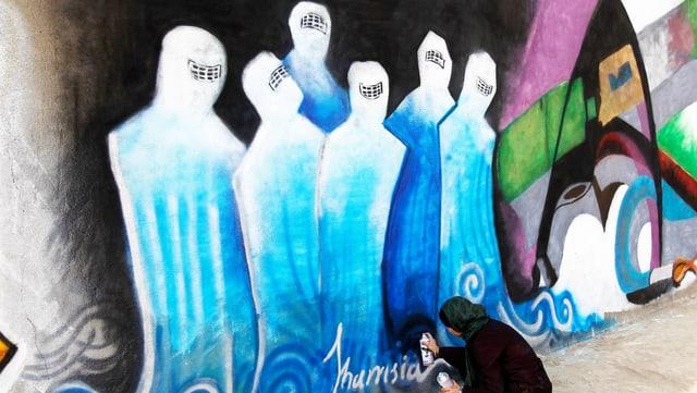 Frau kniet mit Spraydose in der Hand vor einem Graffiti.