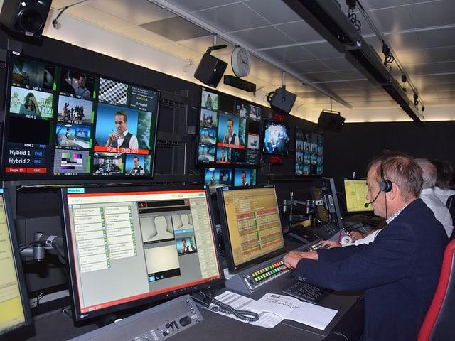 Mann sitzt vor mehreren Computerbildschirmen