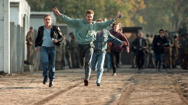 junge Männer rennen freudig eine Strasse entlang