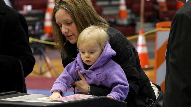 Frau hält Kind. Beide beugen sich über einen Bildschirm. Das Kind hält seine Hand drauf.