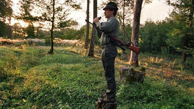 Mann in Jägerkleidung und mit Gewehr steht im Wald auf einem Baumstrunk und hält mit Feldstecher Ausschau