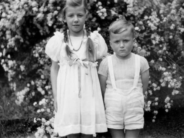 Zwei fein gekleidete Kinder posieren vor der Kamera.