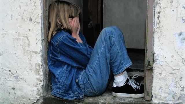 Kind sitzt weinend in einem Eingangsbereich