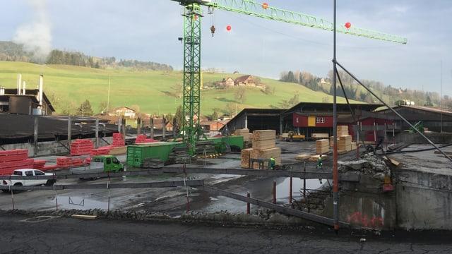Bauplatz mit einem grossen grünen Kranen im Vordergrund.