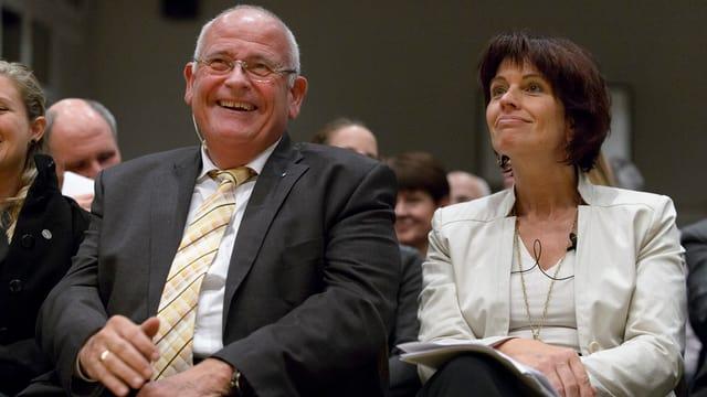 Ein Mann und eine Frau sitzen in einer Turnhalle.